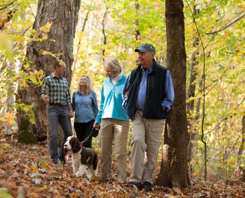 family walking dog in the fall at mountain air
