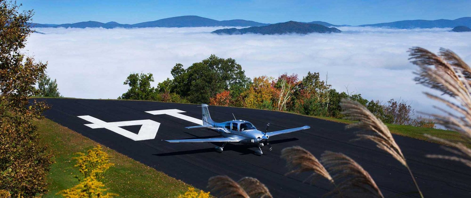 plane landing on private runway at mountain air