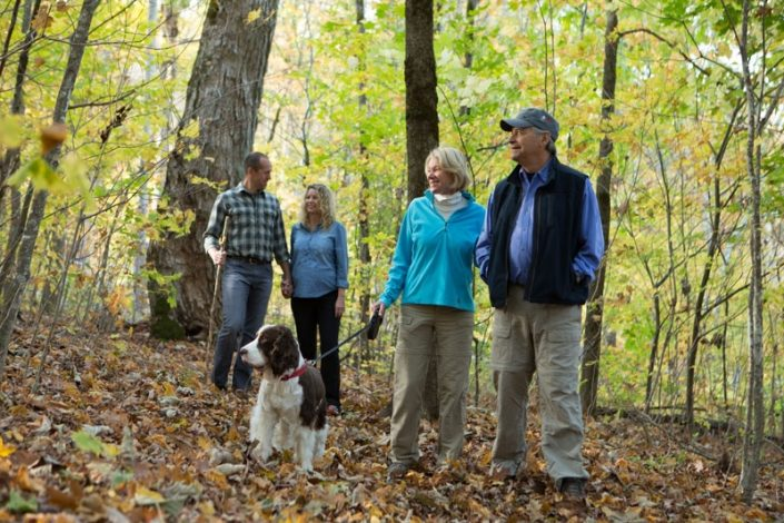 Family With Dog Hiking In The Woods